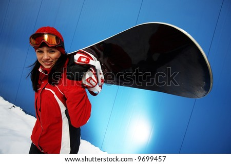 A lifestyle image of a young adult female (age 20-25) snowboarder. - stock photo