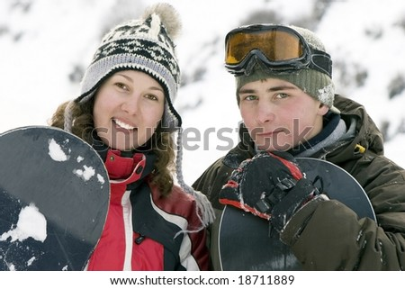 A lifestyle image of two young adult  snowboarders - stock photo