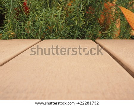 A light brown wood with a green bush and yellow leaves background.  - stock photo