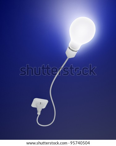 A light bulb connected to an outlet - stock photo