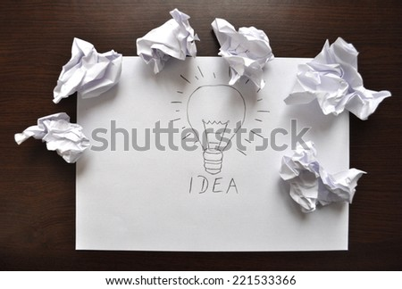 A light bulb drawn on a sheet of paper on which is written idea - stock photo