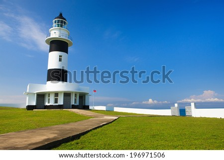 A light house sitting on the edge of the water surrounded by a white fence. - stock photo