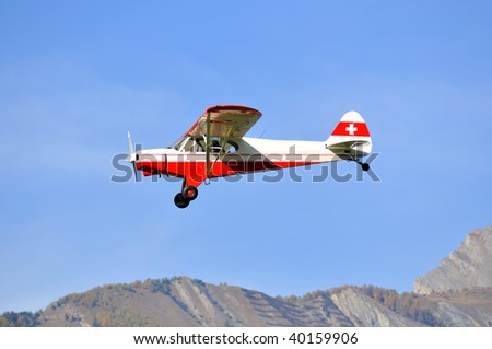 a light single engined aircraft with propellar with mountains in the background - stock photo