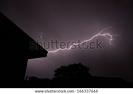 A lightening strikes in a dark sky, around are visible the shapes of some houses and a tree