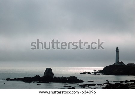A lighthouse on a foggy afternoon in Northern California. I do not know the name of this lighthouse but it is about midway between Santa  Cruz and Half Moon Bay, California. - stock photo