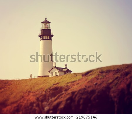 a lighthouse on the cliffs toned with a retro vintage instagram filter effect - stock photo