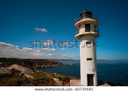 A lighthouse over the rocks against a blue sky with some clouds - stock photo
