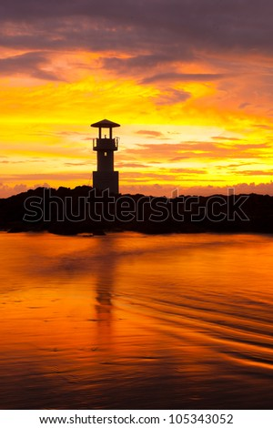 A lighthouse with reflection on wave at beach in the colorful sunset sky. Pung Nga South of Thailand. South East Asia.