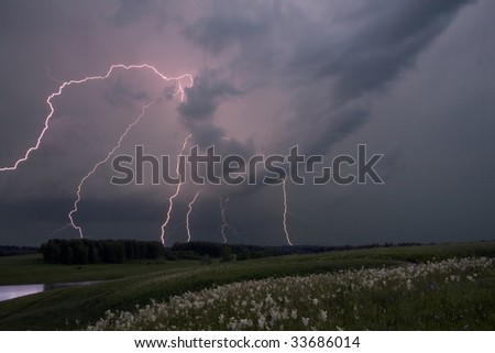 A lightning bolt comes down in a field on a summer day.