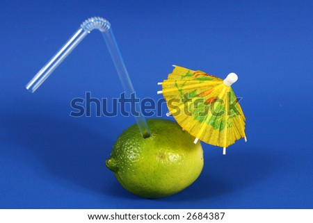 A lime with a straw and drink umbrella, symbolizing either exotic fruit drinks or the inherent health value of the fruit itself. - stock photo