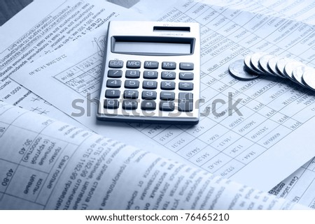 A line of coins and a calculator on business papers - stock photo