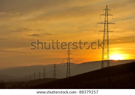 A line of electricity pylons disappearing into the distance at sunset - stock photo