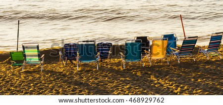 A line of empty beach chairs line the beach at sunrise.