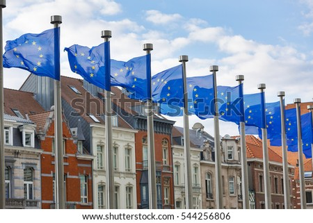 A line of EU flags flying on metal poles in front of the Berlaymont Building in Brussels with traditional houses in the background.