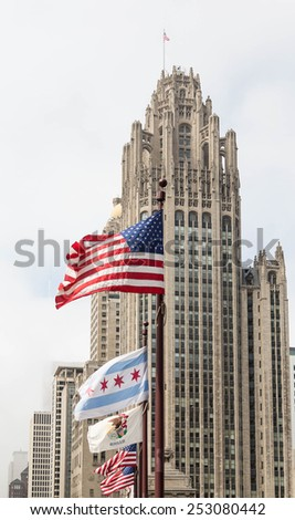 A line of flags in front of classic Chicago skyscraper - stock photo