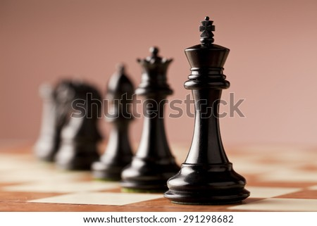 A line of luxurious black Staunton chess pieces carved in genuine ebony wood standing on elm burl and bird's eye maple superior traditional chessboard - stock photo