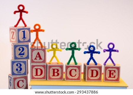 A line of rainbow pipe-cleaner people across ABC and 123 blocks. A lovely photo for international or multicultural ideas and concepts. - stock photo