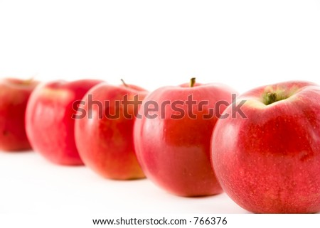 A line of red apples with the focus on the first one - stock photo