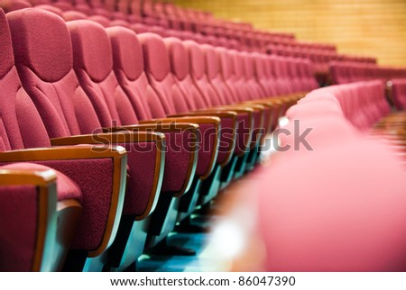 A line of red theatre chairs - short depth of field. - stock photo