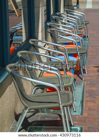 A Line of Shiny Metal and Wicker Chairs on a Brick Street