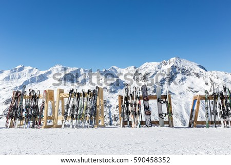 A line of skis and snowboards stored on racks outside a cafe on the slopes at Hochgurgl with the Otztal Alps in the background. All branding and logos removed.