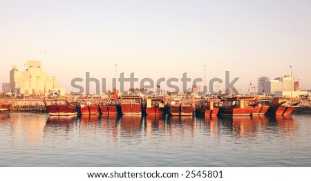 A line-up of dhows in Doha harbour, Qatar, at sunset, with the new Islamic Museum on the left (January 2007) - stock photo
