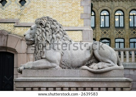 A lion statue sits majesticaly on it's pedestal. - stock photo