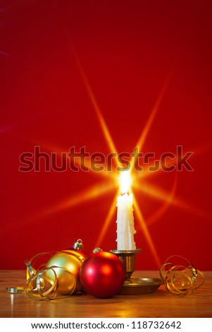 A lit candle in brass holder with Christmas decorations and red background, star filter used during capture for the flame. Copy space to add your own text. - stock photo