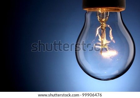 A lit light bulb isolated on white - stock photo