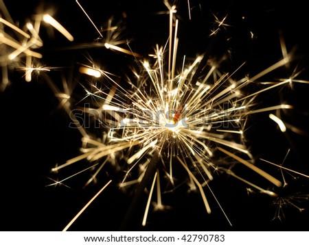 A lit sparkler showing bright sparks - stock photo