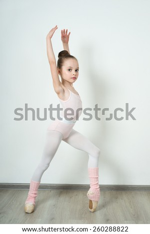 A little adorable young ballerina does ballet poses and stretching exercises on the floor at home - stock photo