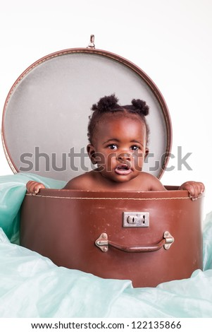 A little African girl in a hat case on a light turqoise organza. - stock photo