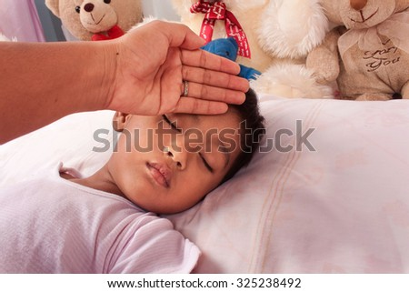 a little asian boy sick mother take care - stock photo