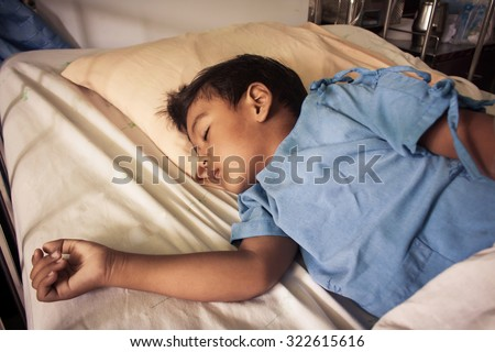a little asian boy sick sleep on the patient bed in the hospital,vintage tone