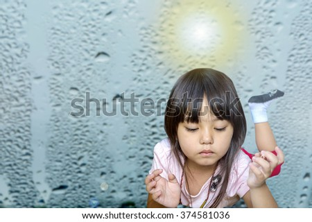 A little asian caucasian girl holding pencil color and thinking face with bright flare over head shows a brilliant idea on blurry rain drops background - stock photo