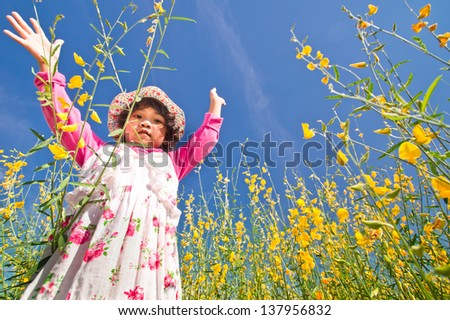 A little Asian girl dancing in the wind with yellow Sunn Hemp flower - stock photo