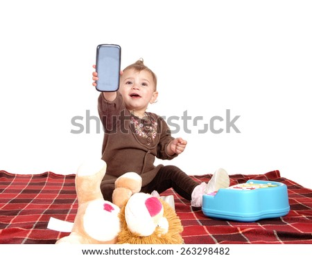 A little baby girl sitting on a blanket on the floor with her toy's and playing with her mom's cell phone, isolated for white background.  - stock photo