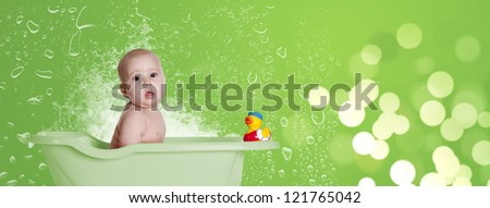 a little baby in her bathtub with her duck - stock photo