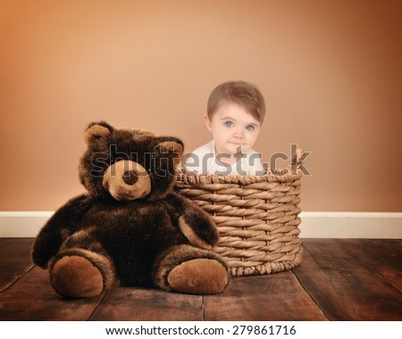 A little baby is sitting on a basket with a teddy bear on a studio brown background for a photography or babysitting concept. - stock photo