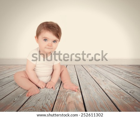 A little baby is sitting on a wooden floor with a blank white wall in the background and looks happy with copyspace for a message. - stock photo
