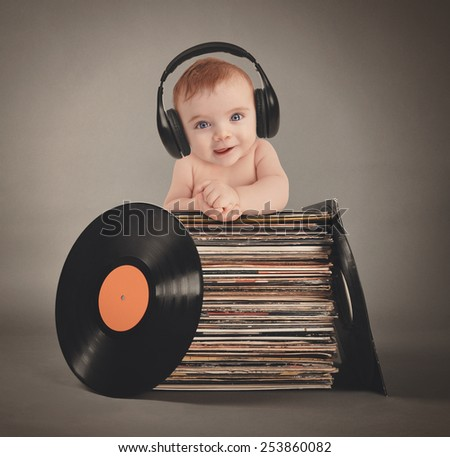 A little baby is wearing music headphones with retro vinyl records on an isolated gray background for a party or entertainment concept. - stock photo