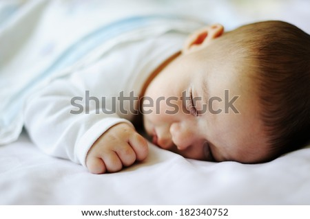 A little baby on sheet in his bed room