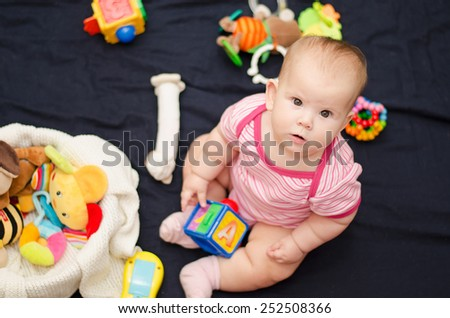 A little baby playing with toys on the floor  - stock photo
