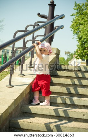 a little beautiful girl on a stairway - stock photo