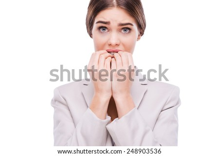 A little bit nervous about this business. Nervous young businesswoman biting her nails while standing against white background - stock photo