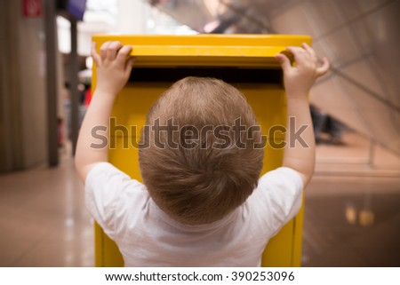 A little blond boy in a white t-shirt puts a letter into a yellow postbox. Sending post to a friend at the post office.  - stock photo
