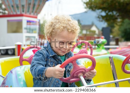 a little blond boy playing in a funfair carousel - stock photo