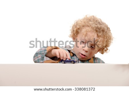 a little blond boy playing with a toy car - stock photo