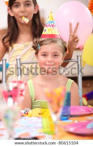 a little blonde girl and her friend doing the v sign posing for her birthday - stock photo