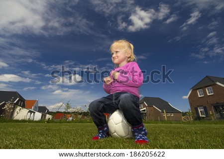 A little blonde girl with blue eyes, pink sweater and wearing no shoes, sits on a soccer ball.  - stock photo